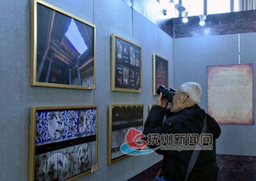 一名老年观众在拍摄展出的图片-